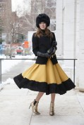 Karolina Gliniecka in an Aryton hat and jacket with a Louis Vuitton clutch